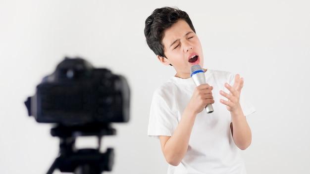Middelgrote jongen zingen op camera Gratis Foto
