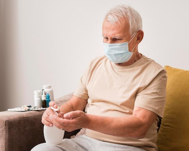 Middelgrote man die ontsmettingsmiddel gebruikt Gratis Foto