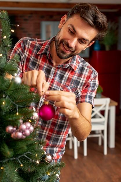 Middelgrote shot gelukkig man versieren van de kerstboom Gratis Foto