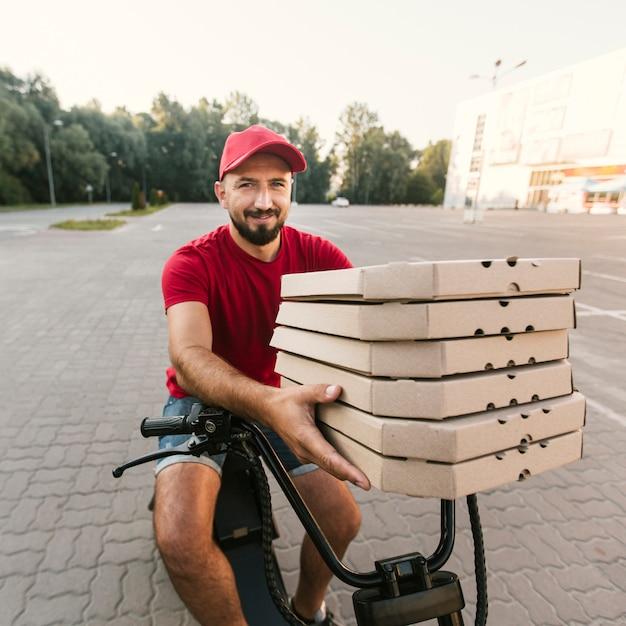 Middelgrote shotdelivery kerel die pizzadozen houdt Gratis Foto