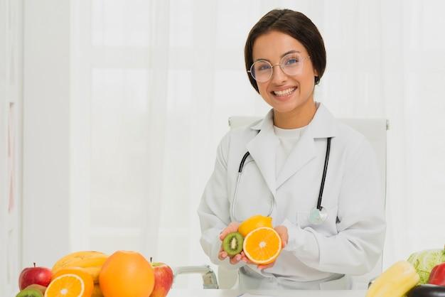 Middellange geschoten gelukkige arts met sinaasappel en kiwi Gratis Foto