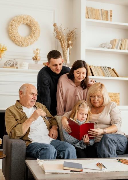 Middellange geschoten gelukkige familie met boek Premium Foto