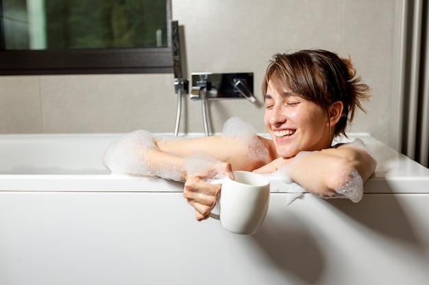 Middellange geschoten gelukkige vrouw in de badkuip Gratis Foto