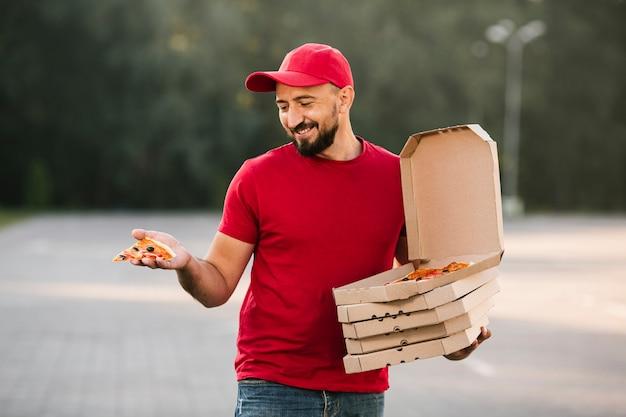 Middellange geschoten leveringskerel die pizzaplak bekijken Gratis Foto
