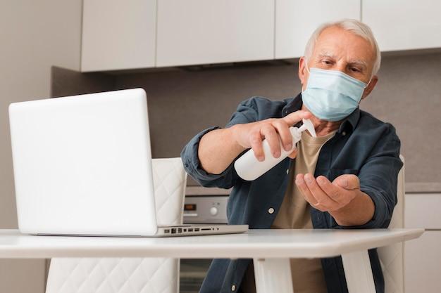 Middellange geschoten oude man die ontsmettingsmiddel gebruikt Gratis Foto