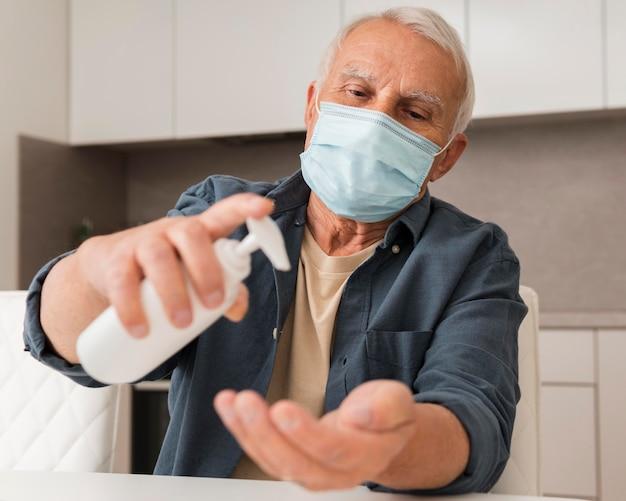 Middellange geschoten oude man die ontsmettingsmiddel giet Gratis Foto