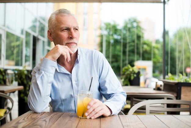 Middellange geschoten oude mens die bij restaurant denkt Gratis Foto