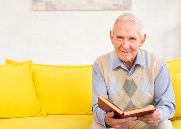 Middellange geschoten oude mens die een boek leest Gratis Foto