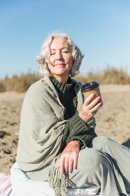 Middellange geschoten oude vrouw met koffiekop Gratis Foto