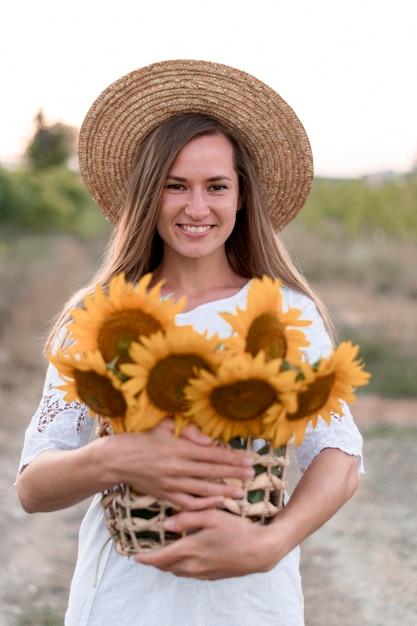Middellange geschoten smileyvrouw die in openlucht stelt Premium Foto