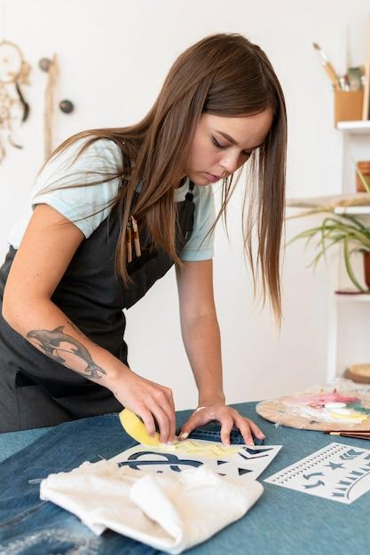 Middellange geschoten vrouw die jeans met spons schildert Gratis Foto