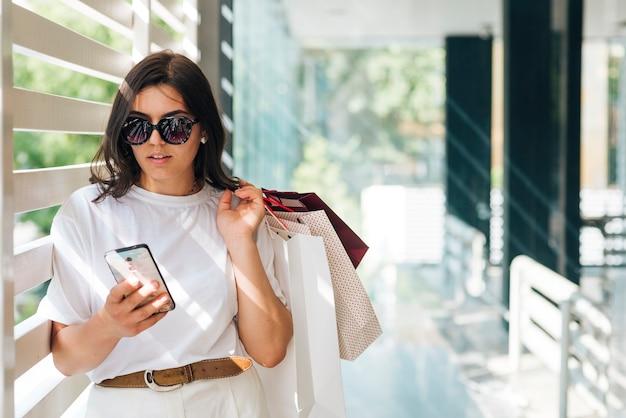 Middellange geschotene vrouw die op de telefoon kijkt Gratis Foto