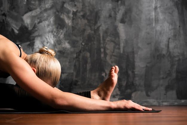 Middellange geschotene vrouw die op de vloer legt Gratis Foto