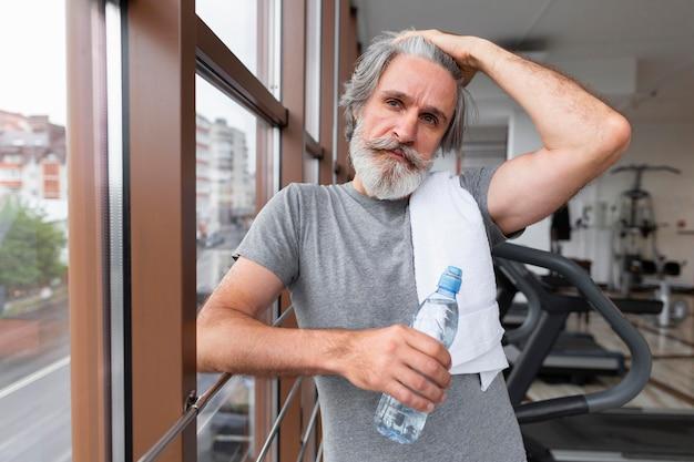 Middellange shot fit man op sportschool Gratis Foto