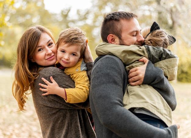 Middellange shot gelukkige ouders die kinderen knuffelen Premium Foto