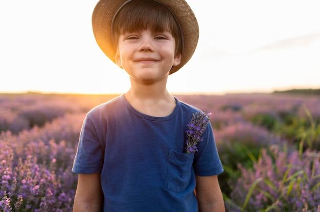 Middellange shot jongen poseren in bloem veld Gratis Foto