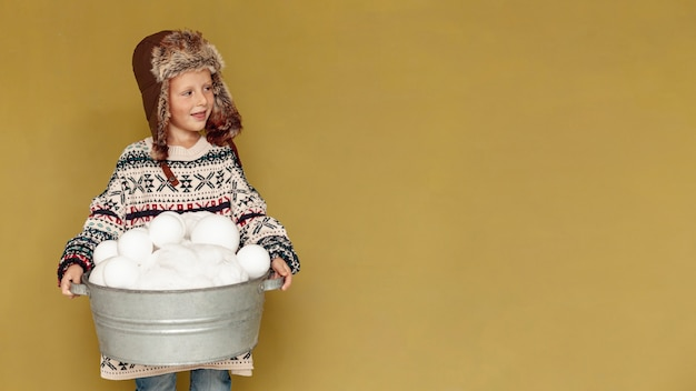 Middellange shot kind met sneeuwbal en kopie-ruimte Gratis Foto
