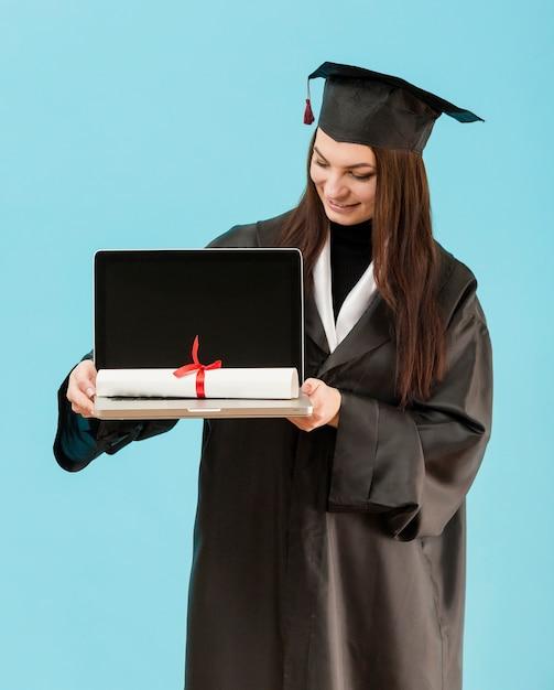 Middellange shot laptop van de meisjesholding Gratis Foto