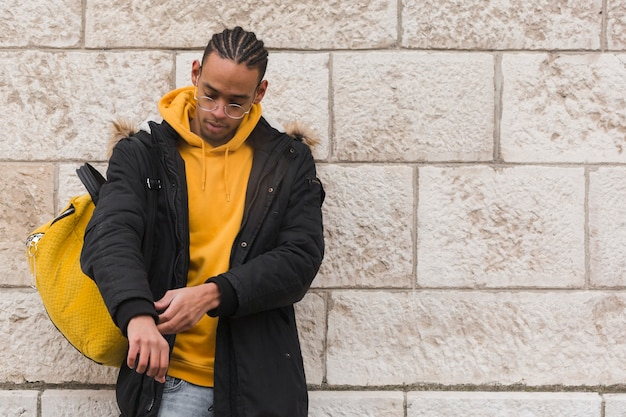 Middellange shot man met gele rugzak en hoodie Gratis Foto