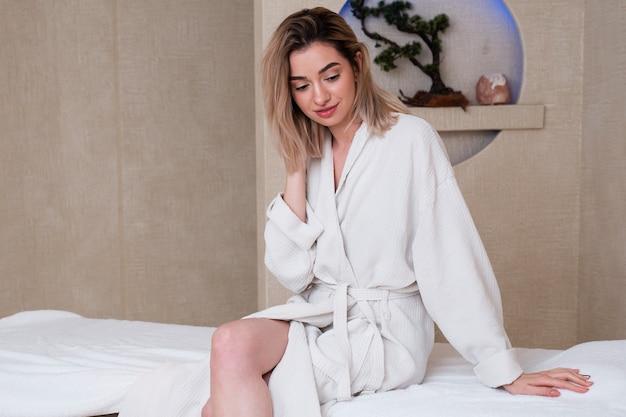 Middellange shot meisje met badjas binnenshuis Gratis Foto