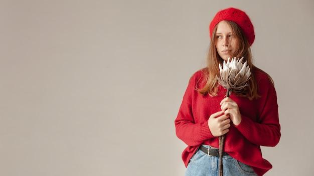 Middellange shot meisje met rode hoed en bloem poseren Gratis Foto