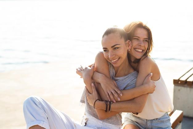 Middellange shot smiley vrouw knuffelen haar vriend Gratis Foto