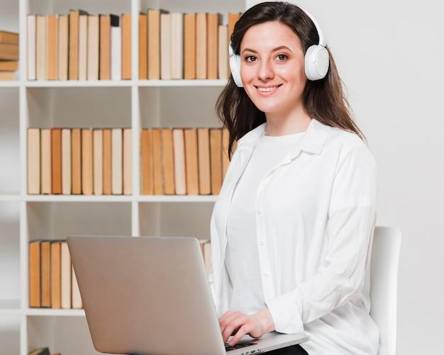 Middellange shot student in een bibliotheek e-learning concept Gratis Foto