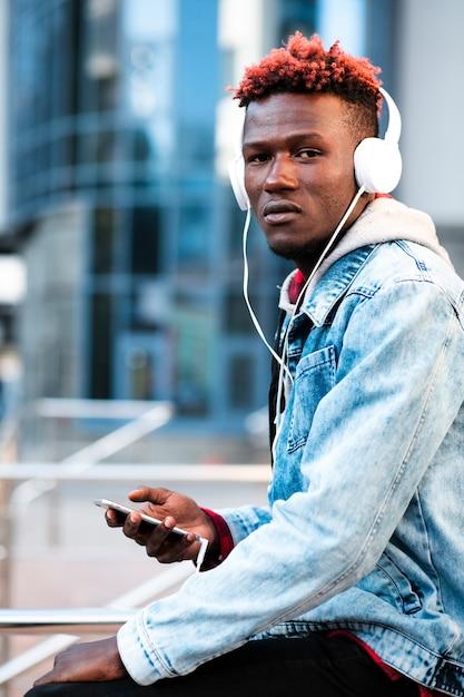 Middellange shot trendy man met koptelefoon en smartphone Gratis Foto