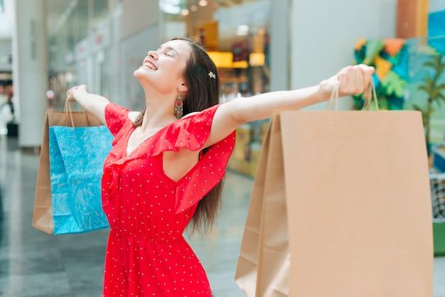 Middelmatig schotmeisje dat blij in het winkelcentrum voelt Gratis Foto