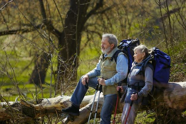 Midden in de natuur. leeftijd familie paar man en vrouw in toeristische outfit wandelen op groen gazon in de buurt van bomen in zonnige dag. concept van toerisme, gezonde levensstijl, ontspanning en saamhorigheid. Gratis Foto