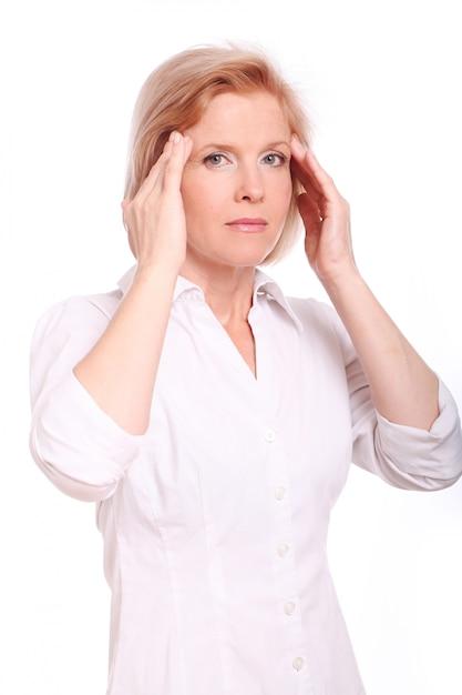 Midden oude vrouw die hoofdpijn over witte achtergrond heeft Gratis Foto