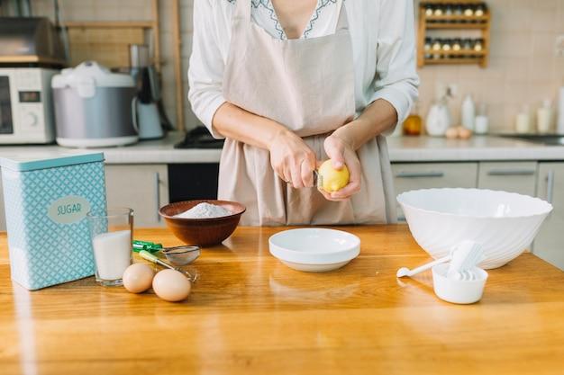 Middensectie van een vrouwengrating citroen terwijl het voorbereiden van cake Gratis Foto