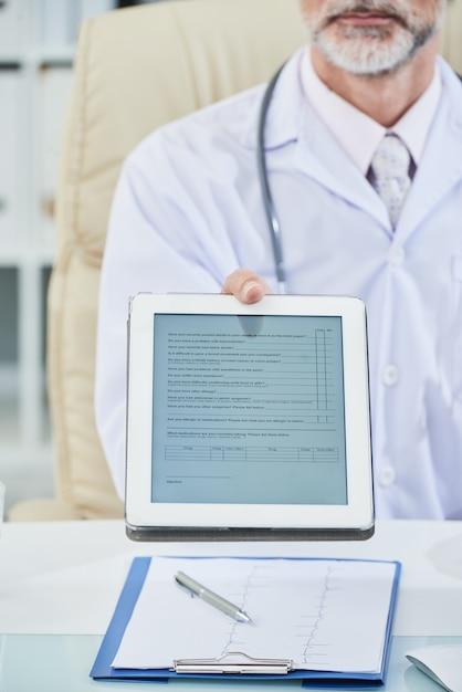 Middensectie van mannelijke arts gezeten aan bureau dat de digitale vragenlijst op het tabletscherm uitbreidt tot de camera Gratis Foto