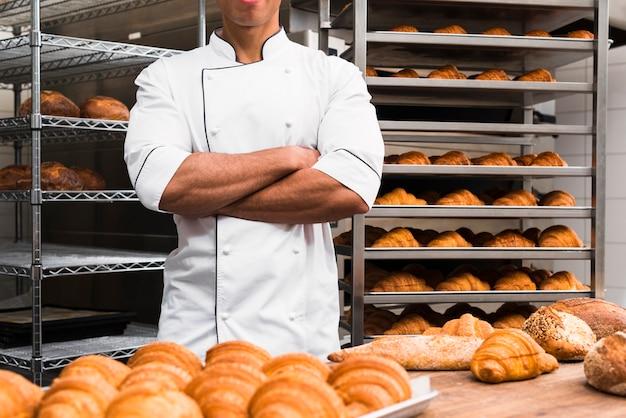 Midsection van een mannelijke bakker met zijn gekruiste wapens status in bakkerij Gratis Foto