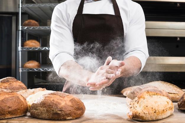 Midsection van een mannelijke bakkershand die de bloem op houten bureau met gebakken brood bestrooien Gratis Foto