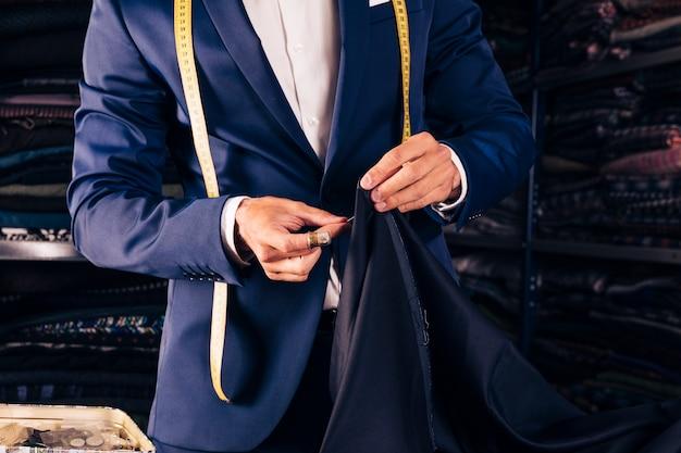 Midsection van een mannelijke naaiende de manierstof van de manierontwerper met naald Premium Foto