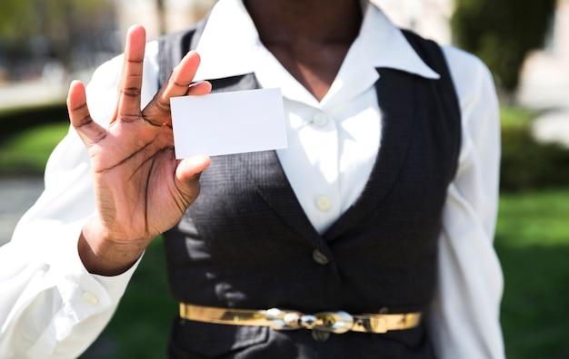 Midsection van een onderneemster die wit visitekaartje toont Gratis Foto
