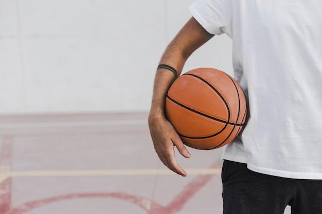 Midsectionmening van de hand van een man met basketbal Gratis Foto