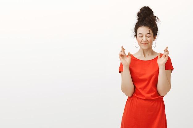 Mijn wens komt zeker uit. grijnzende gelukkige europese vrouw in rode jurk met haar in een broodje gekamd Gratis Foto