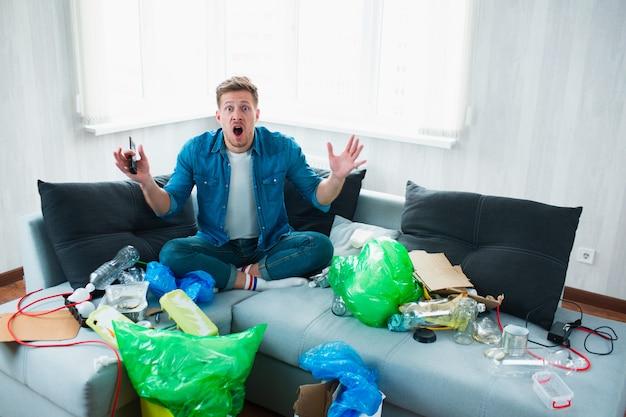Milieuvervuiling concept. geschokt jongeman. hij weet niet wat hij moet doen met de vervuiling van zijn appartement en de hele wereld Premium Foto