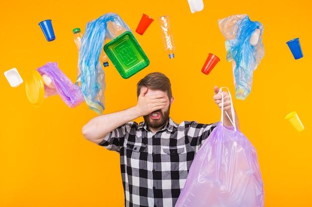 Milieuvervuiling, plastic recyclingprobleem en ecologieprobleemconcept - droevige mens die vuilniszak houdt en zijn ogen bedekt met palm op gele muur. Premium Foto