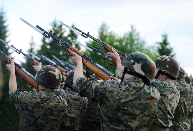 Militairen met militair camouflageuniform in openinegeweren van legervorming vuur Premium Foto