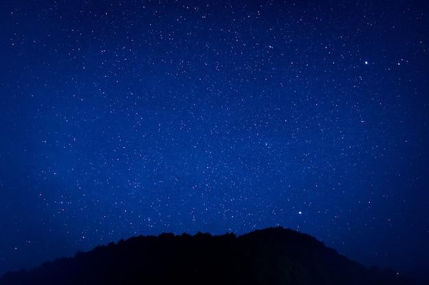 Miljoenen sterren schijnen in de duisternuchthemel op mooie aardachtergrond. Premium Foto