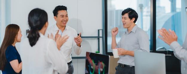 Millennial groep van jonge ondernemers azië zakenman en zakenvrouw vieren het geven van vijf na de deal gelukkig gevoel en ondertekening van contract of overeenkomst in de vergaderzaal in kleine moderne kantoor. Gratis Foto