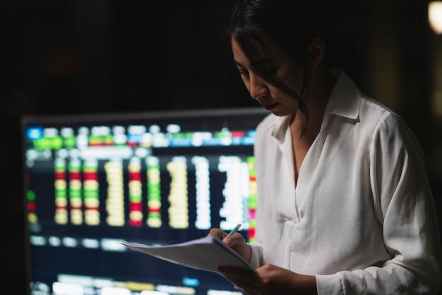 Millennial jonge chinese zakenvrouw werken 's avonds laat stress met project onderzoeksprobleem op laptop in de vergaderzaal op kleine moderne kantoor. azië mensen beroepsgebrek syndroom concept. Gratis Foto