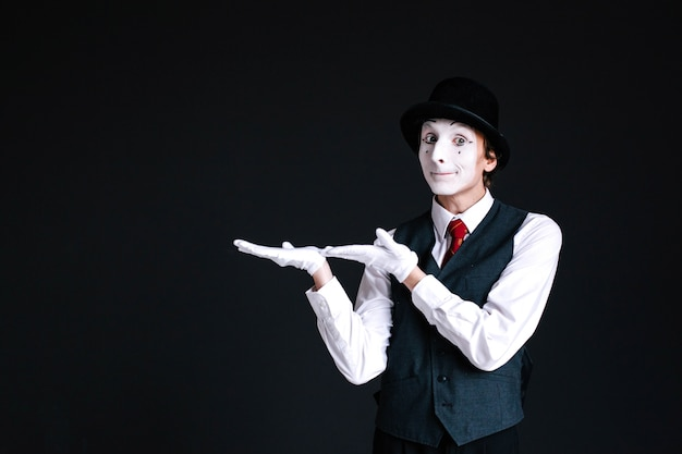 Mime houdt iets onzichtbaar op zijn handpalmen Gratis Foto