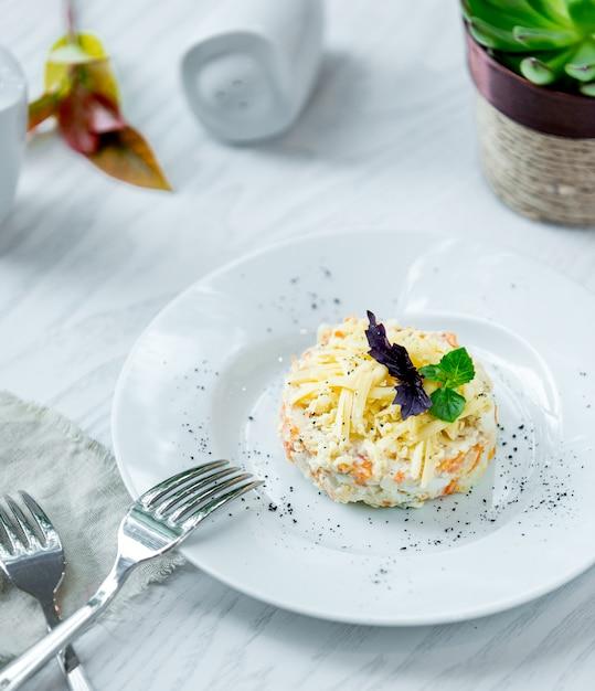 Mimosasalade met gehakte parmezaanse kaas en kruiden. Gratis Foto