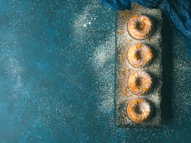 Mini bundt ring cakes met sinaasappelschil poedersuiker op donkerblauw en serveerbord. bovenaanzicht. holiday kerst zoete voedsel afgezwakt Premium Foto