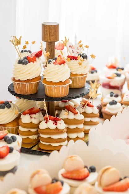 Mini chocolade cupcakes gegarneerd met mini roze donuts op een dessert tafel Premium Foto