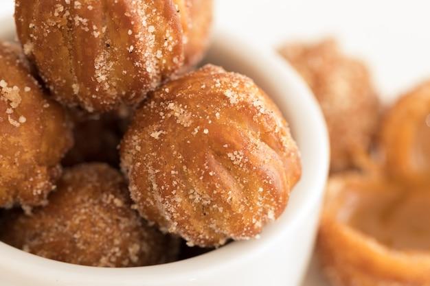 Mini churros gevuld met dulce de leche (melkkaramel) Premium Foto